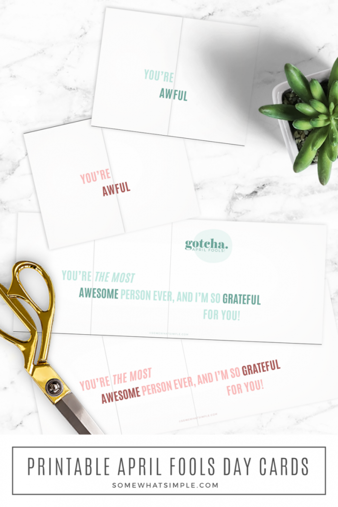 long image of some april fools day cards laying on the counter next to gold scissors and a green plant