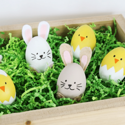 easter eggs decorated like bunnies and chicks in a brown bow with fake grass