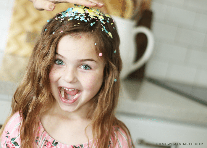 a hand smashing a yellow cascarone on the head of a cute little girl and confetti is all over her head. Her mouth is open and she has a surprised look on her face.