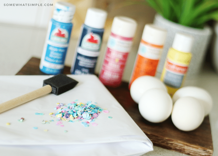 Bottles or different colored craft paint, a foam pain brush, confetti and eggs on a counter which are some of the supplies you will need for this project.
