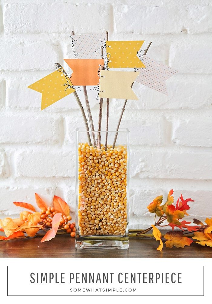 a fall table centerpiece made with a vase full of popcorn kernels and pennants stuck inside.