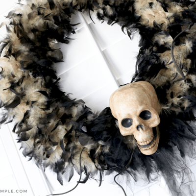 black halloween wreath with a fake skull attached with black ribbon