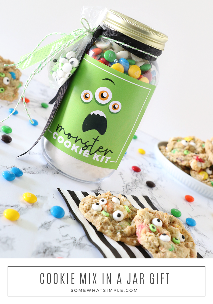 monster cookie mix in a mason jar with finished cookies sitting next to the jar