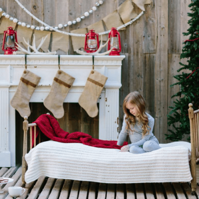 little girl sitting on bed on christmas morning