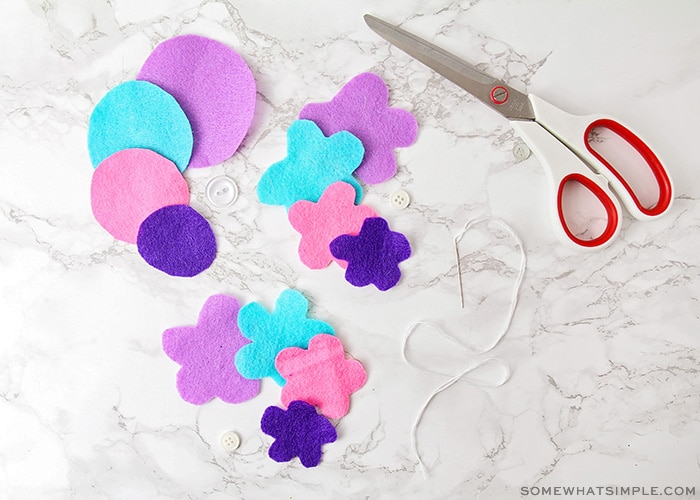 brightly colored felt shapes with scissors and thread