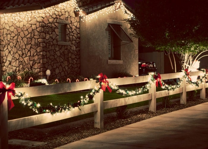 Christmas lights photography tips - white fence with garland and christmas lights outside at night