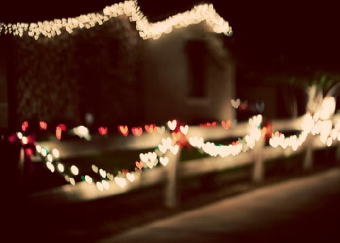 how to take better christmas photos with red and white christmas lights outside on a fence
