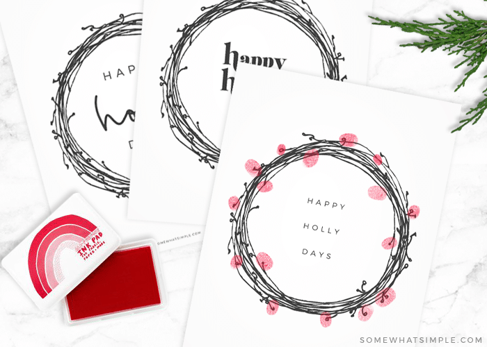 3 wreath prints, one with red fingerprints stamped around it to look like holly berries
