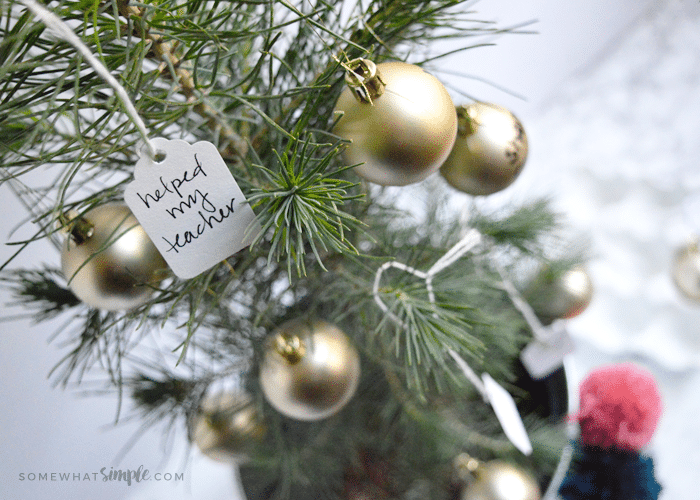"""a small christmas tree with acts of service written on tags """"The Giving Tree"""""""