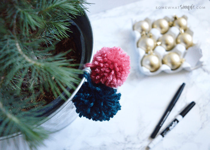 pink and blue pom poms hanging from a christmas tree