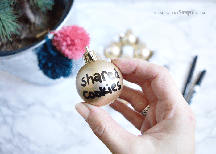 a gold ornament with a kind act written in black marker