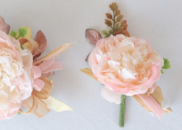 a light pink flower made into a boutonnière with greenery