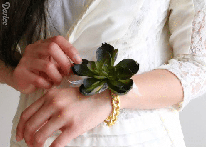 a woman wearing a white dress with a succulent corsage on her wrist