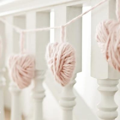 hearts made out of yarn hanging on a banister. diy valentine decor