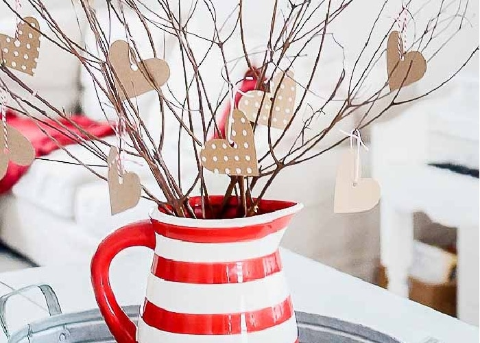 branches from a tree in a red and white vase with paper hearts stuck to the branches