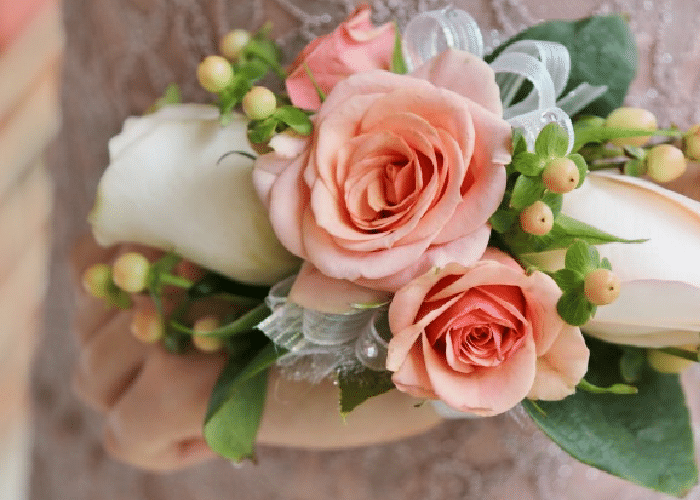 a prom corsage with peach and white roses