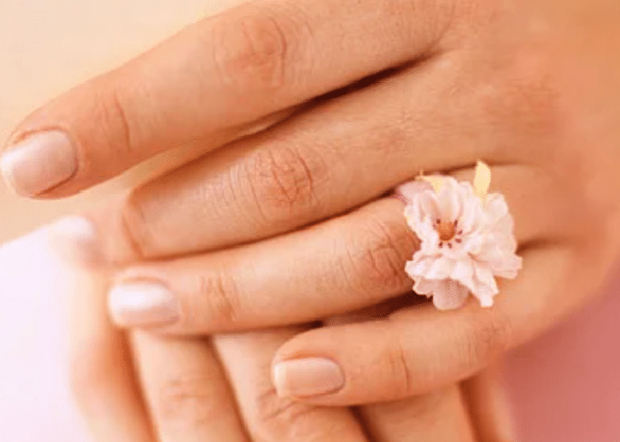 2 hands crossed over each other with a fabric flower ring on one finger