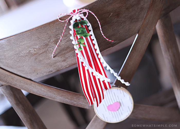 fabric and paper heart wreath hanging on the back of a chair