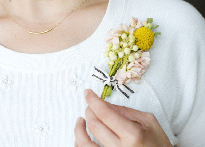 a woman wearing a white sweater and simple corsage.