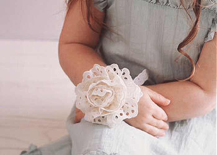 A little girl wearing a corsage on her wrist made out of ribbon