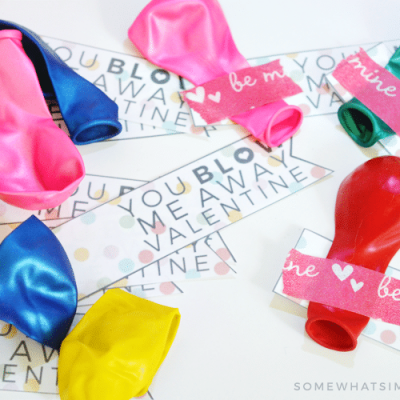 "balloons taped to valentine tags that say ""you blow me away"""