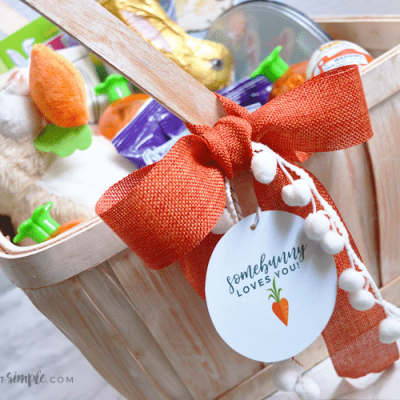 brown easter basket filled with goodies and tied up with an orange ribbon and printable gift tag