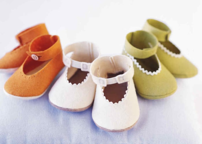 3 pairs of handmade baby shoes on a blue blanket