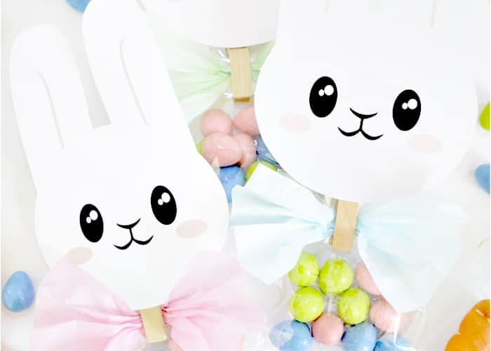 2 paper bunnies attached to treat bags with a wood clip
