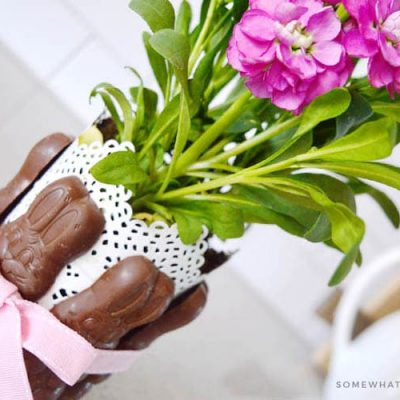 chocolate bunnys tied around a vase of flowers with a pink ribbon