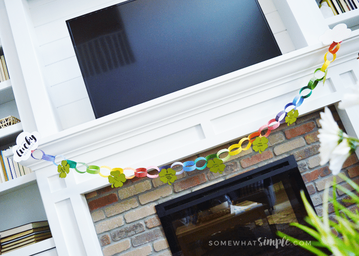 a colorful paper garland hanging from a mantle