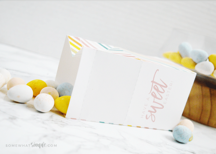 easter treat box laying on its side with candy eggs spilling out