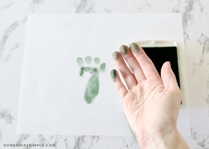 making footprints with a childs hand and a stamp pad