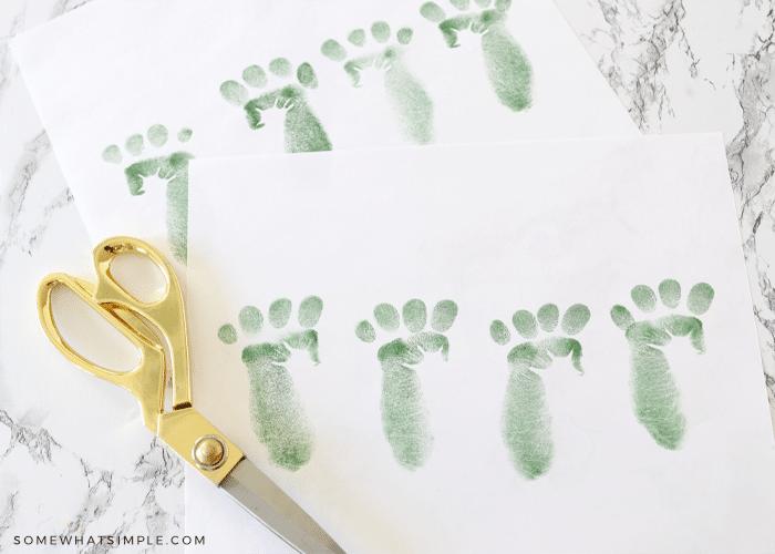 gold scissors next to a paper of green leprechaun footprints