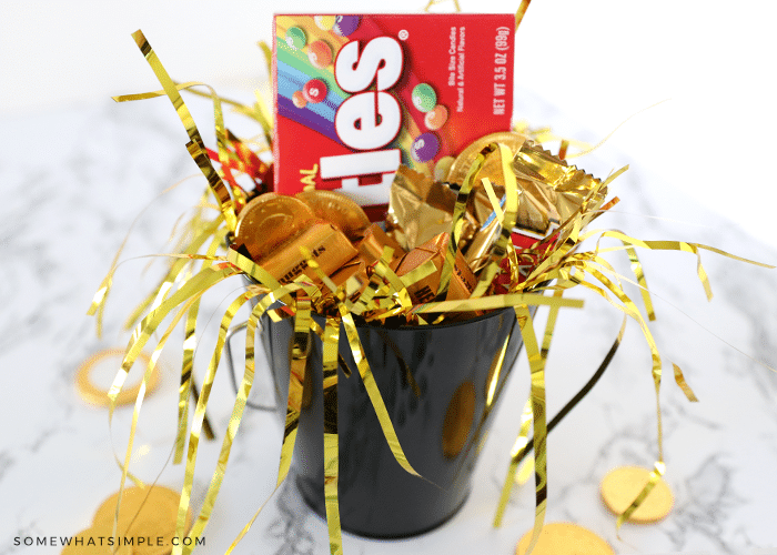 black tin bucket filled with gold confettit and candies