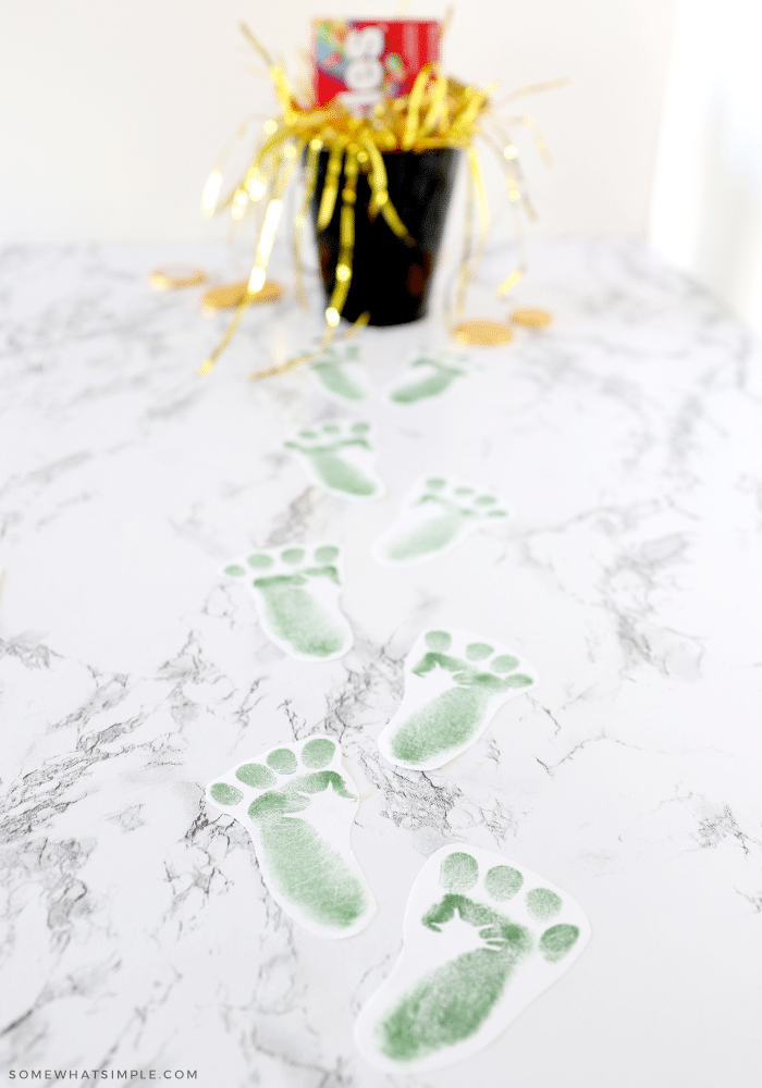 green footprints leading up to a pot of gold