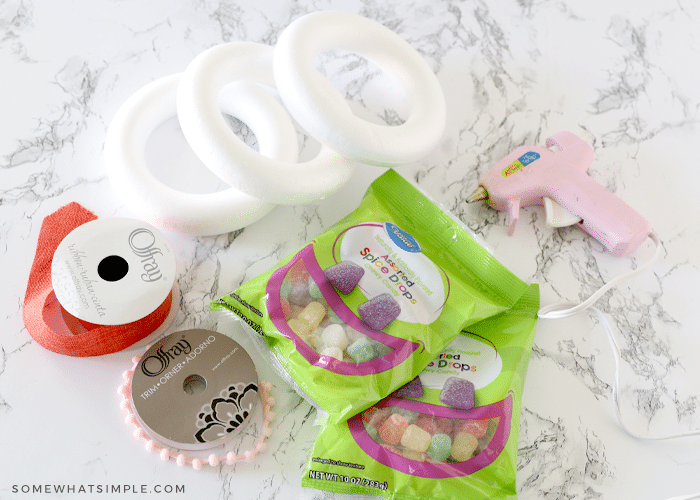 ribbon, wreath forms, hot glue and gumdrops on a counter