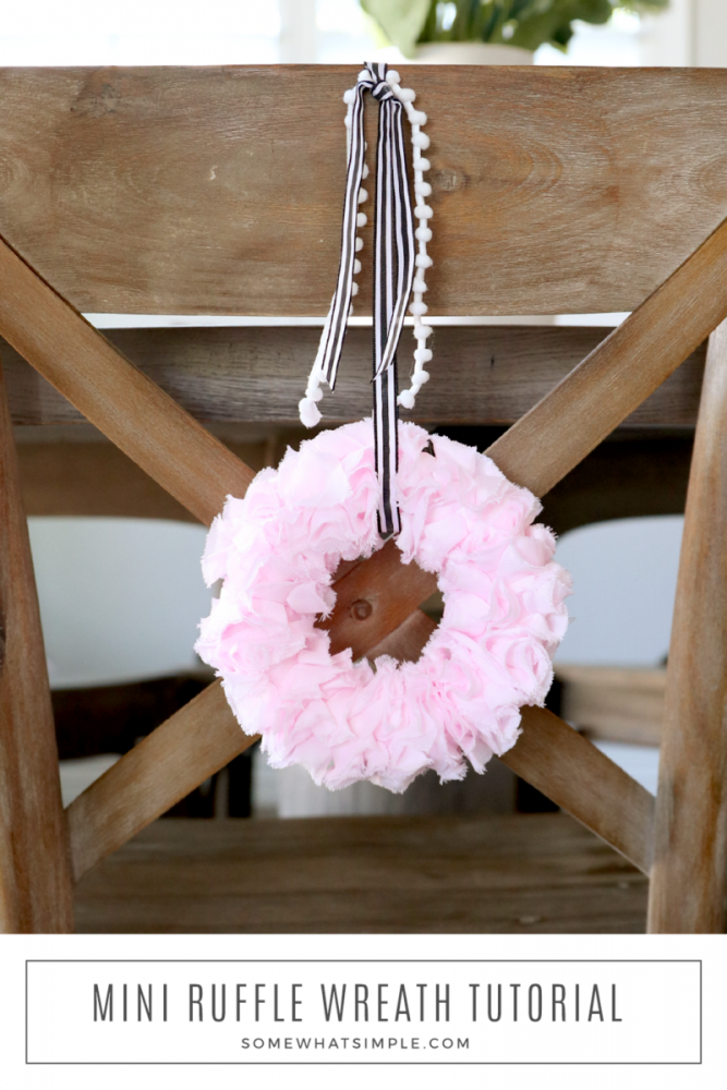mini pink ruffle wreath handing on the back of a chair