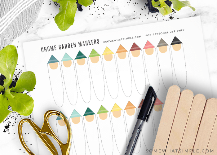 printable gnome plant markers next to craft sticks, scissors, and a black sharpie marker
