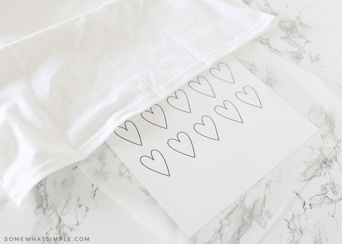 white tshirt laying on a counter with a piece of coloring paper being inserted inside it