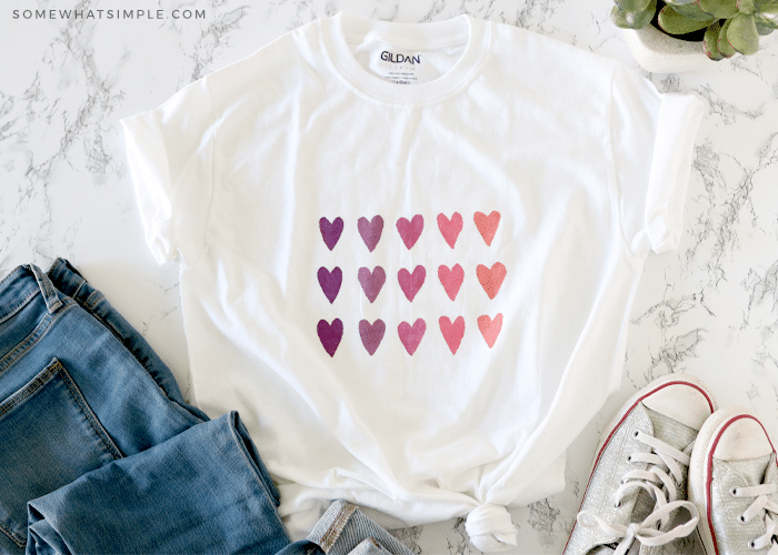 watercolor shirt with colorful hearts laying next to a pair of tennis shoes and jeans