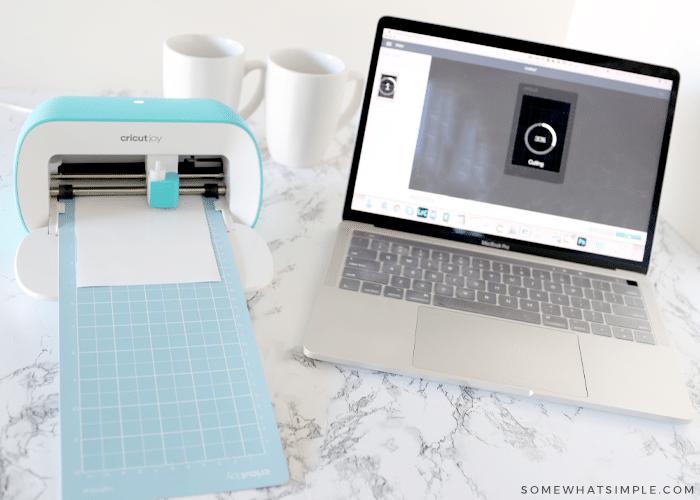 cutting machine next to a laptop cutting some white vinyl