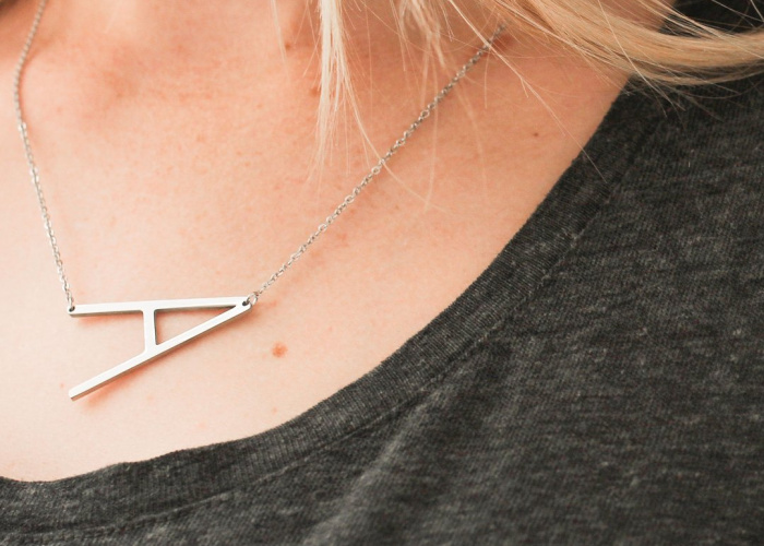 gold initial necklace on woman