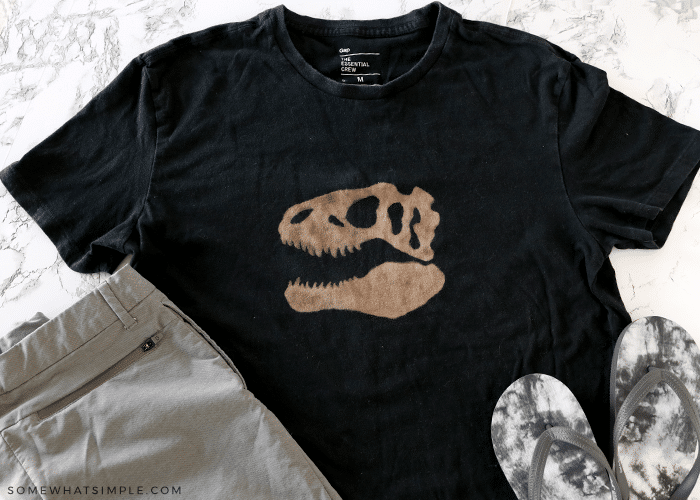 black shirt with brown dinosaur on it
