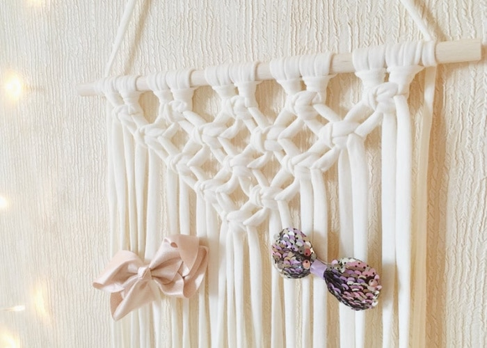 macrame wall hanging with bows clipped to the yarn