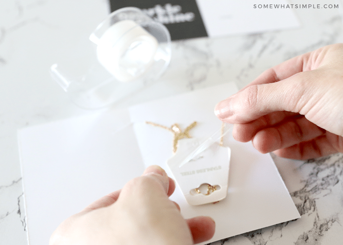 Wrap the back of the necklace to fit within the card and tape in place