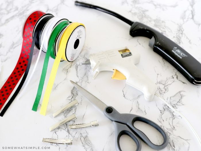 ribbon, scissors, glue gun and lighter on the counter