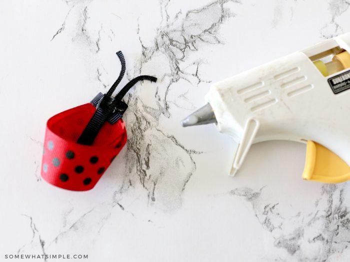 glueing ribbon antennae to a ladybug bow