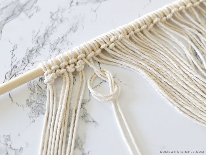tying a knot in rope on a wood dowel