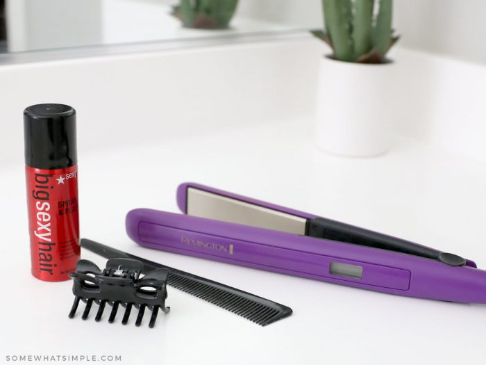 hair spray, comb, clip and flat iron on a bathroom counter