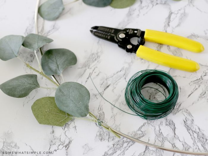 placing greenery on a wreath form with wire
